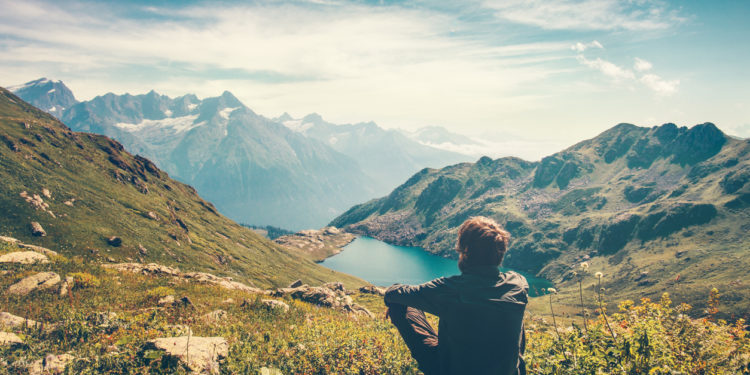 Young man traveling and looking at beautiful mountain scenery
