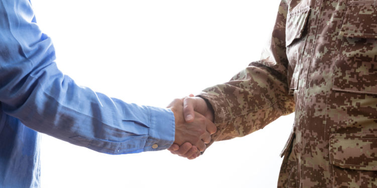 Military person and civilian shaking hands standing on white background.