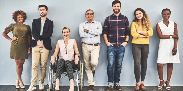 Shot of a diverse group of businesspeople standing against a wall